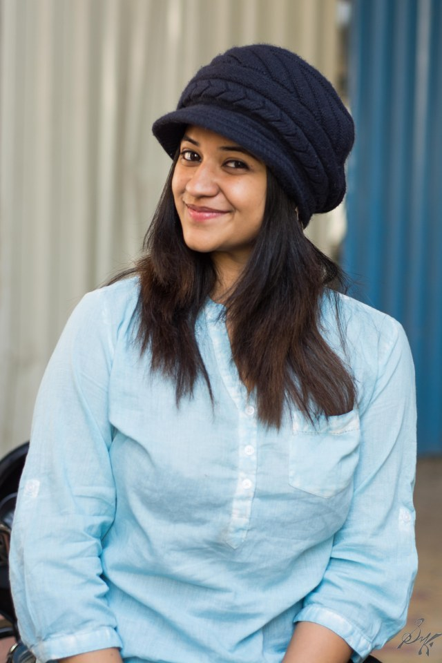 Girl sitting looking pretty has a smile wearing a beanie