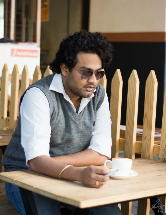 Man sitting in a coffee shop with cigarette in hand thinking about past