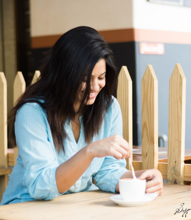 Girl stirring coffee has a smile on her face