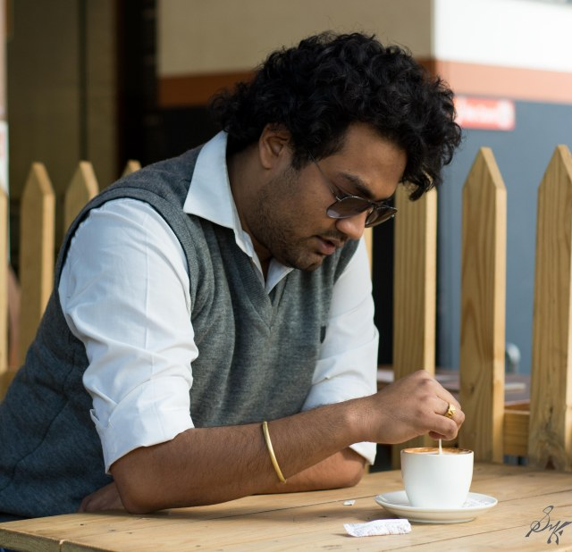 Man stirring coffee thinking deeply