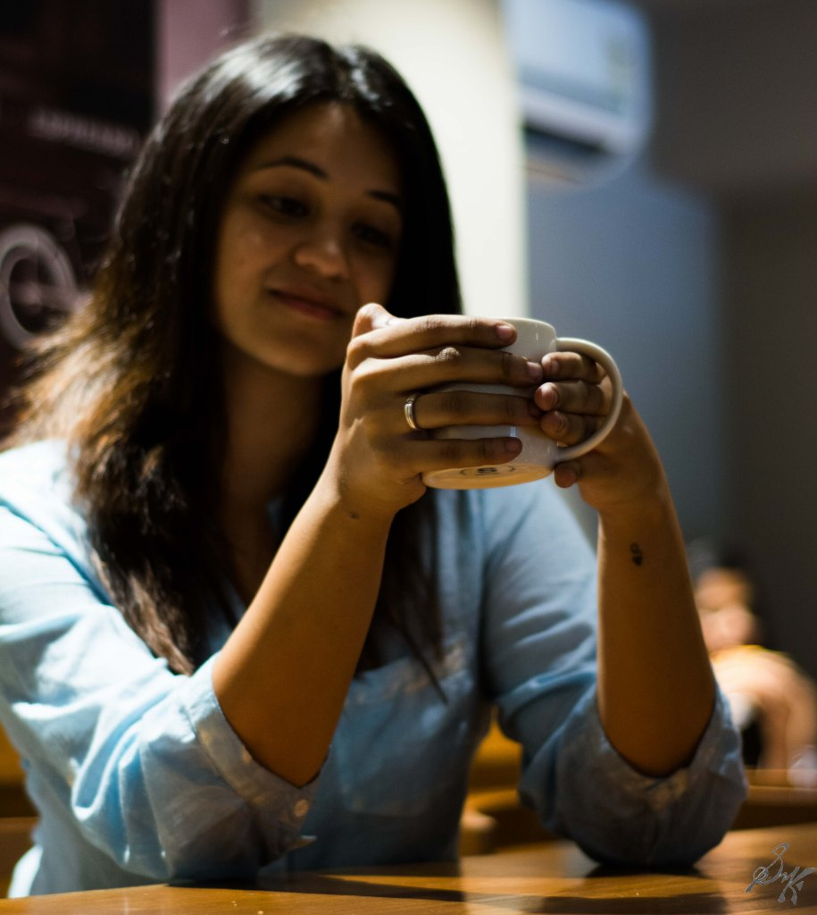 Woman with a cup of coffee with focus on engagement ring