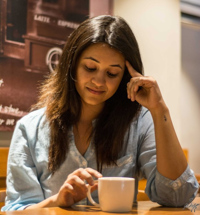 Girl sitting in a coffee shop thinking of past
