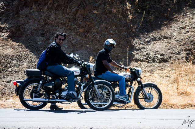 Two men posing with Royal Enfield Bullet