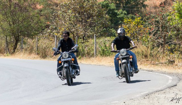 Two men on Royal Enfield Bullet taking a turn
