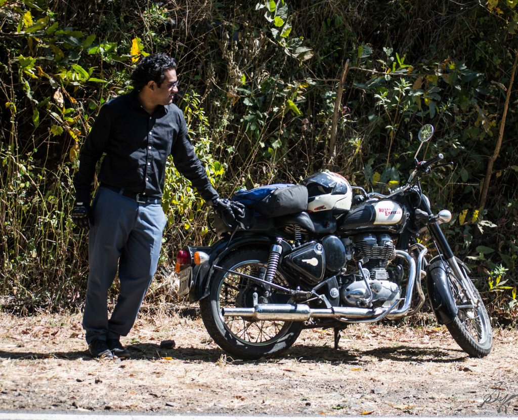 Man posing with a Royal Enfield Bullet
