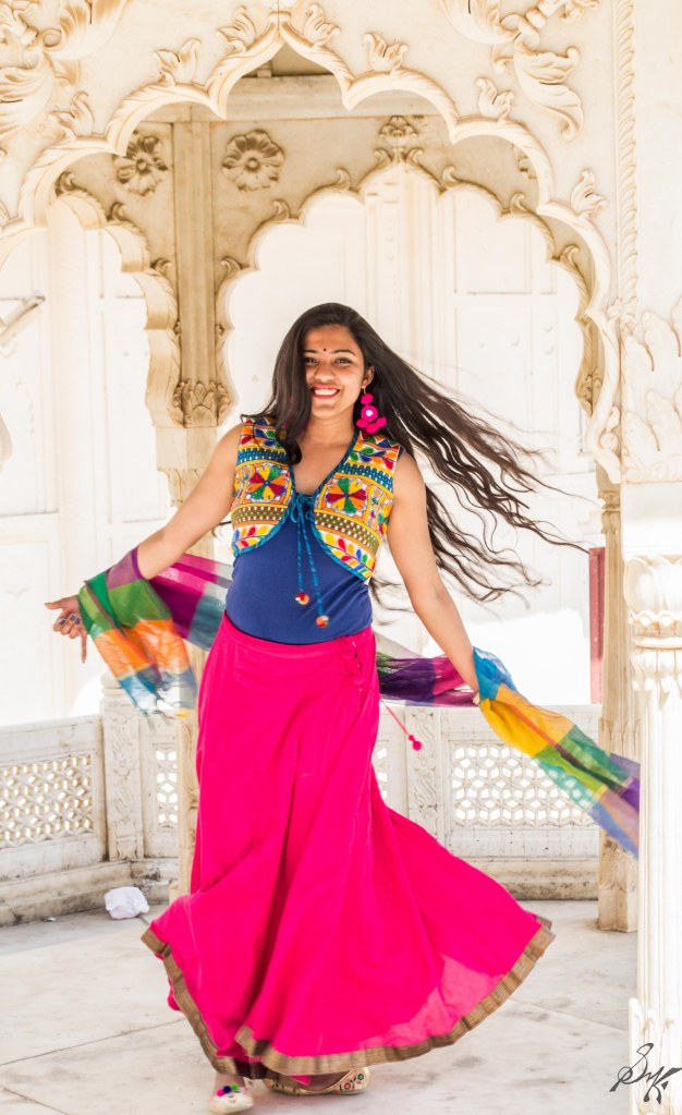 Girl happily spinning near the columns, City Palace, Alwar, Rajasthan