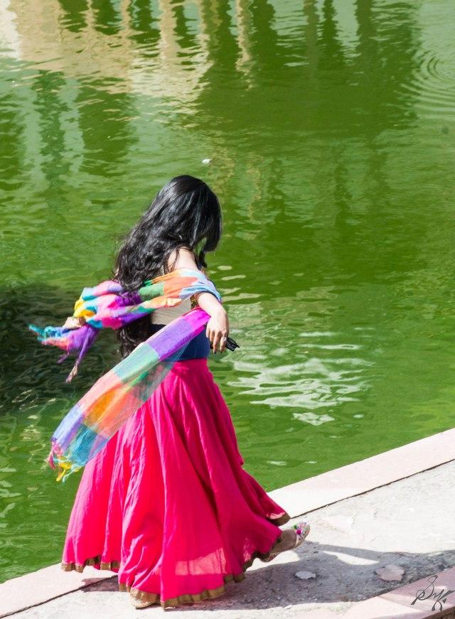 Girl walking near the lake at Musi Maharani cenotaph, City Palace, Alwar, Rajasthan