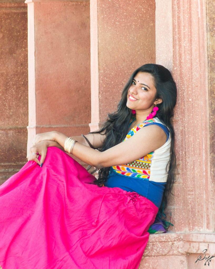 Girl sitting and smiling at cenotaph of Musi Maharani, City Palace, Alwar, Rajasthan