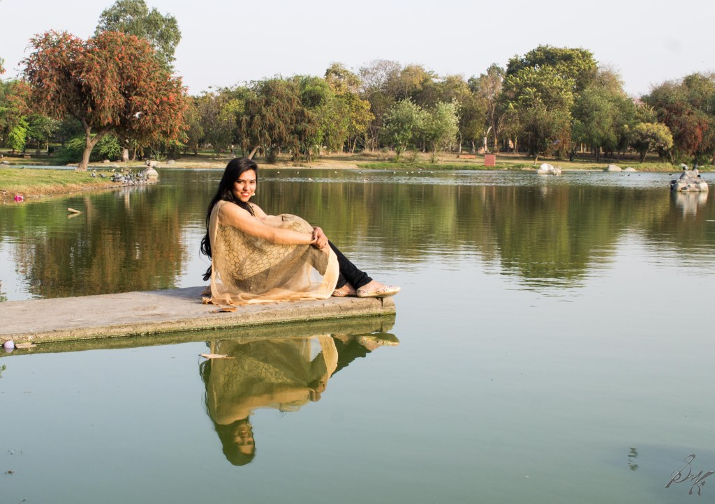 Girl sitting on the edge of a lake and relections, Rajghaat, New Delhi, India