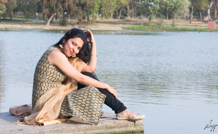 Girl sitting on the  edge of water playing with her hair, Rajghaat, New Delhi, India
