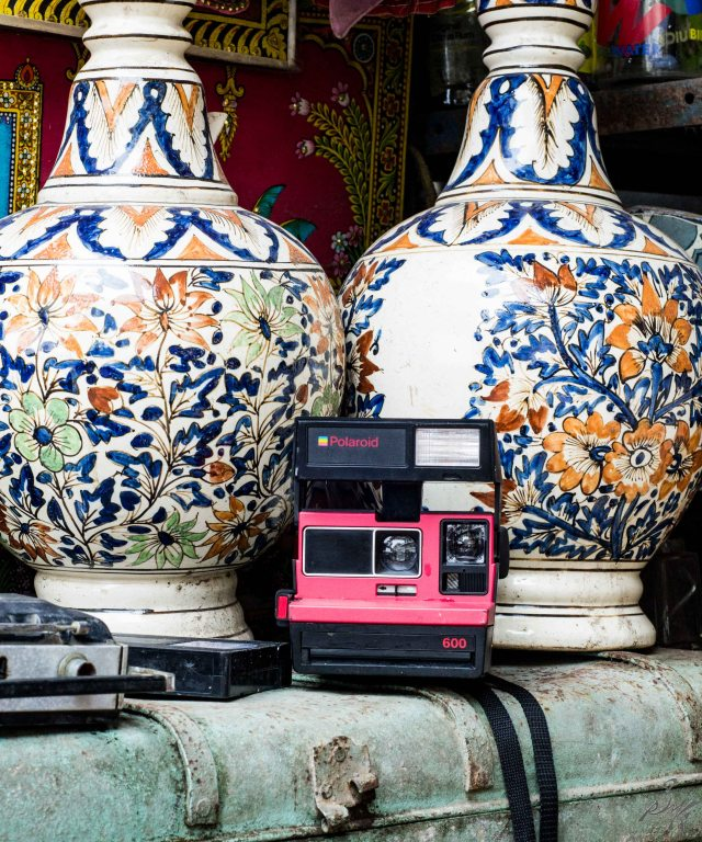 Polaroid Camera in Front of Vases