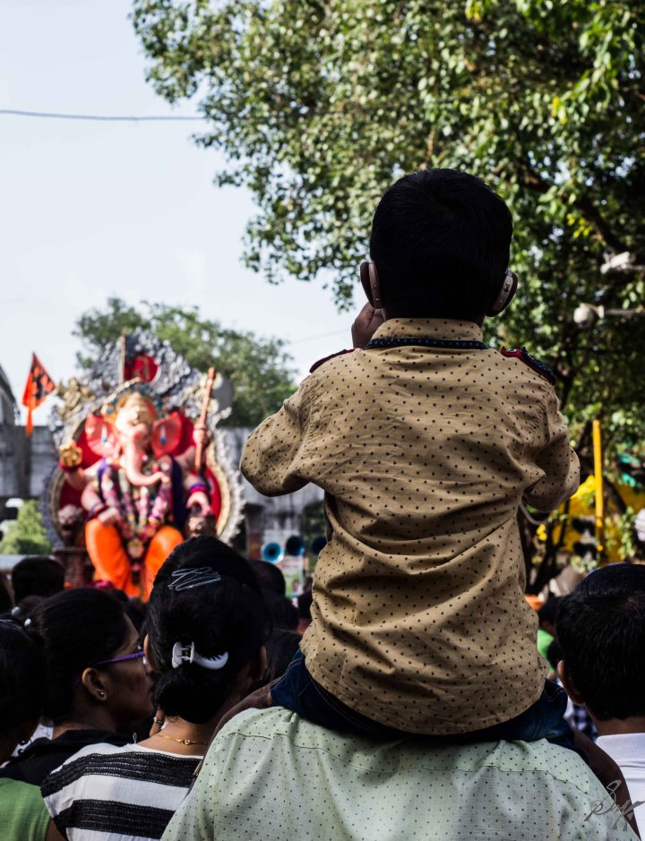 A boy sits on his father's shoulder during the Visarjan