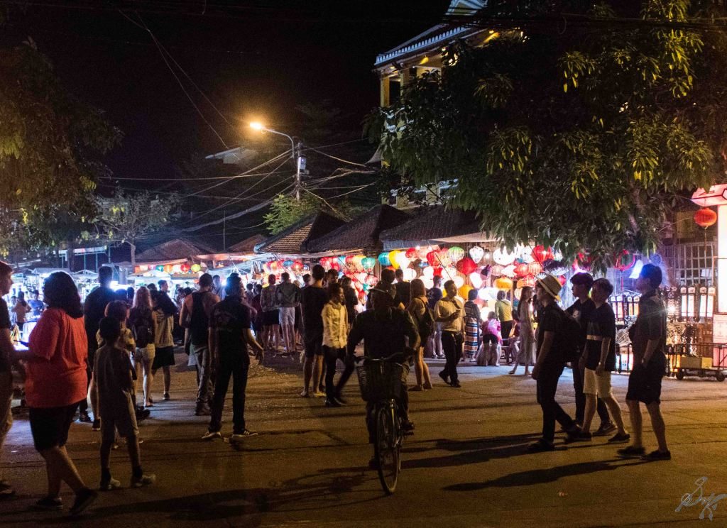 Busy street with tourists and locals, lights, food, Hoi An, Vietnam