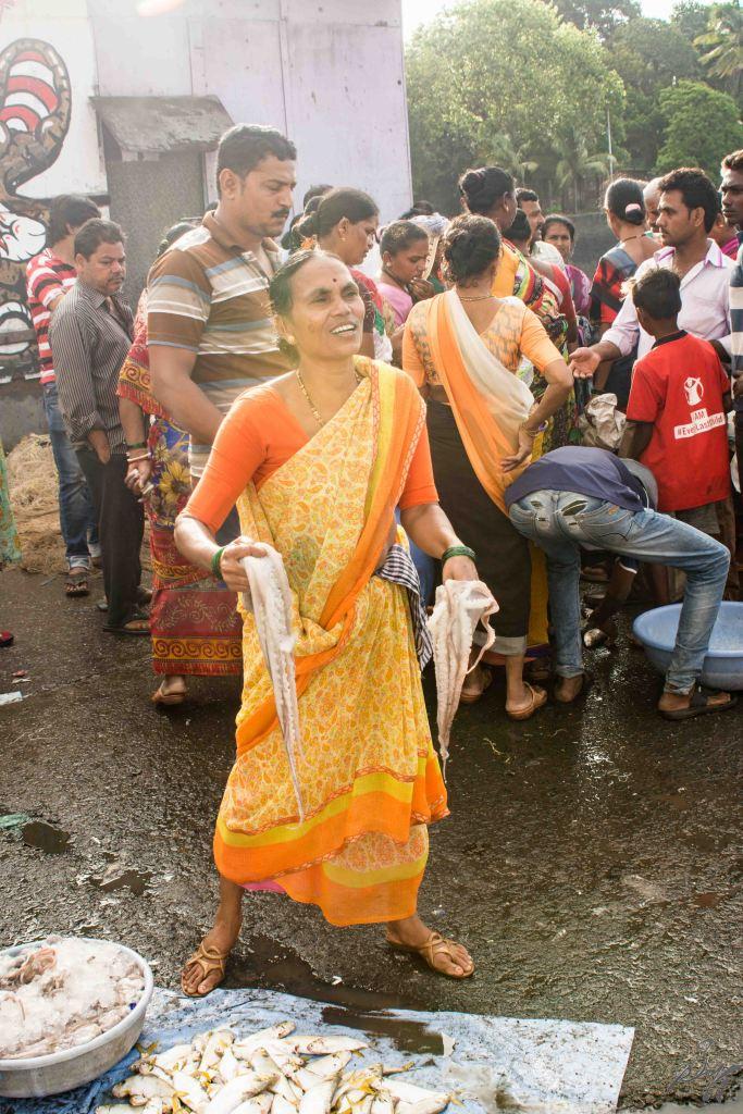 Lady holds up octopus for display, Sassoon Docks, Mumbai, India