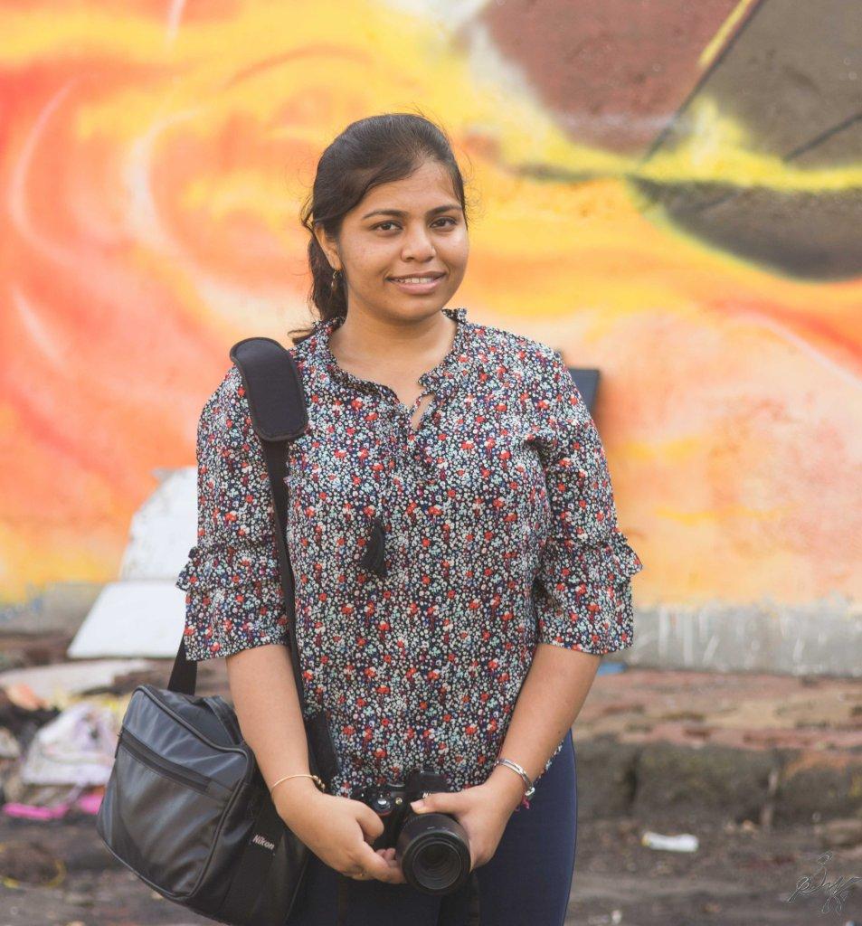 Haldar posing in front of a wall art, Sassoon Docks, Mumbai, India